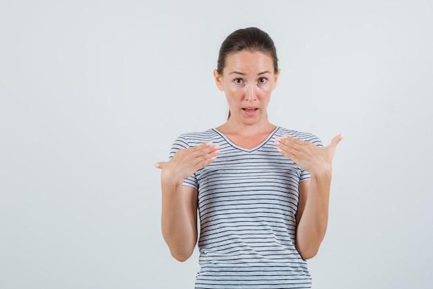 Jovem fêmea apontando para si mesma em vista frontal da camiseta listrada.