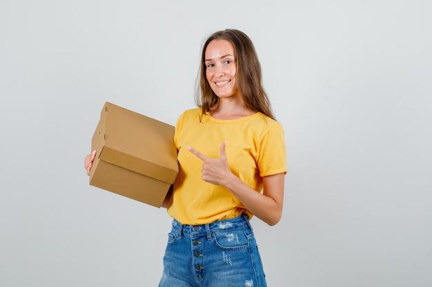 Jovem fêmea apontando para uma caixa de papelão em t-shirt, shorts e parecendo feliz. vista frontal.