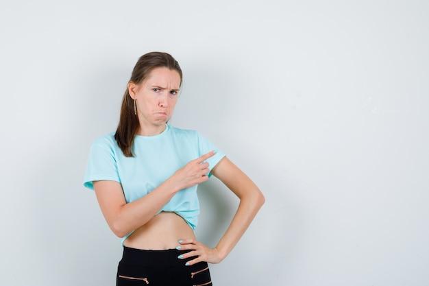 Jovem fêmea bonita apontando para o canto superior direito em t-shirt, calça e olhando mal-humorada, vista frontal.