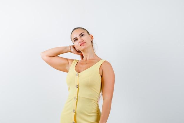 Jovem fêmea bonita mantendo a mão atrás da cabeça no vestido e olhando pensativa, vista frontal.
