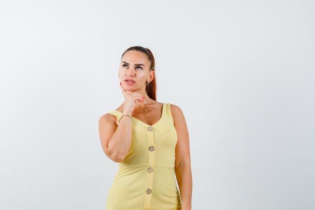 Jovem fêmea bonita mantendo o dedo na bochecha no vestido e olhando pensativa. vista frontal.