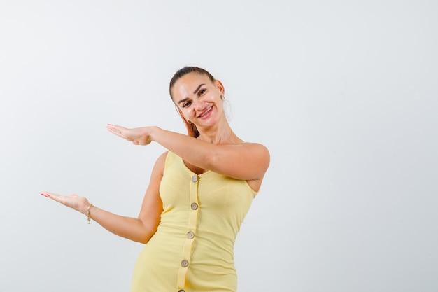 Jovem fêmea bonita mostrando tamanho cadastre-se no vestido e olhando feliz. vista frontal.