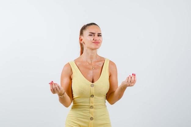 Jovem fêmea bonita no vestido fazendo gesto de dinheiro e olhando com problemas, vista frontal.
