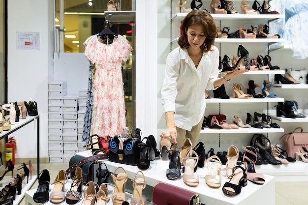 Jovem fêmea bonita olha saltos pretos nas prateleiras das lojas