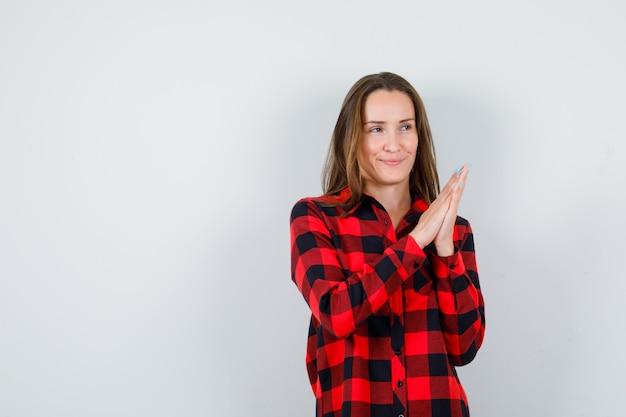 Jovem fêmea bonita pressionando as mãos juntas em uma camisa casual e olhando alegre, vista frontal.