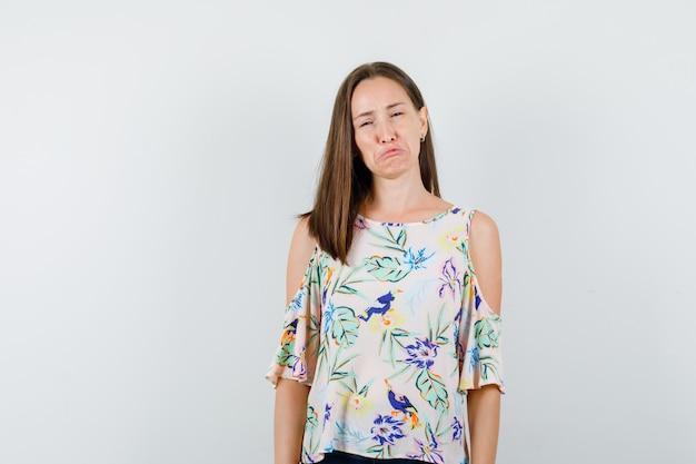 Jovem fêmea chorando na camisa e olhando desesperada, vista frontal.