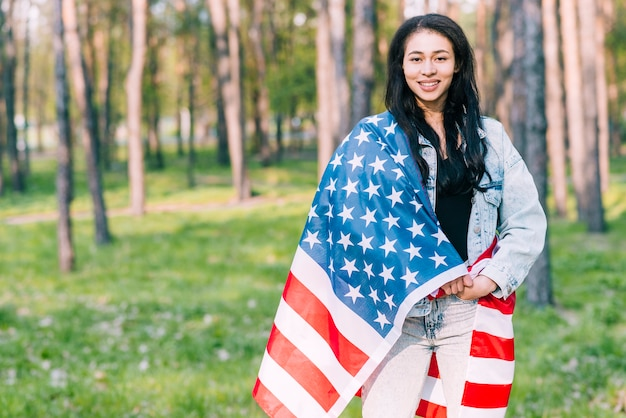 Jovem fêmea coberta com a bandeira dos eua