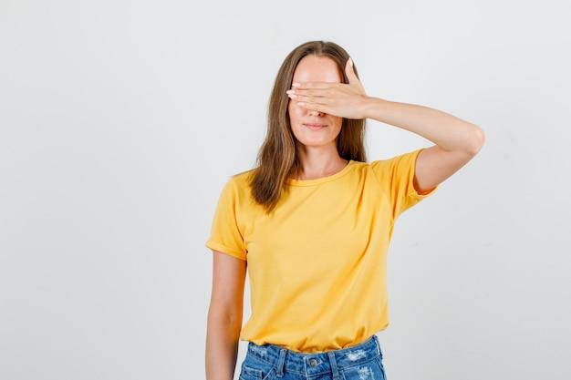 Jovem fêmea cobrindo os olhos com a mão na t-shirt, vista frontal do calção.