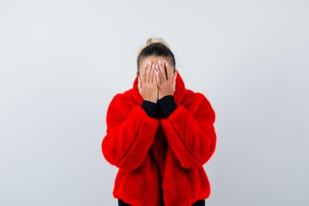 Jovem fêmea com as mãos no rosto de suéter, casaco de pele vermelha e olhando com medo, vista frontal.