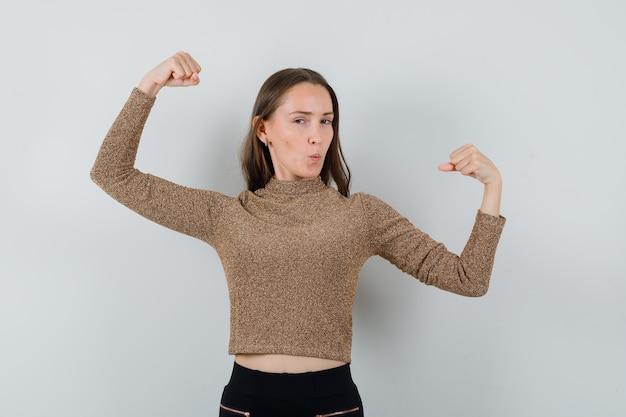 Jovem fêmea com blusa dourada, levantando os braços enquanto mostra seu poder e está impressionante, vista frontal.