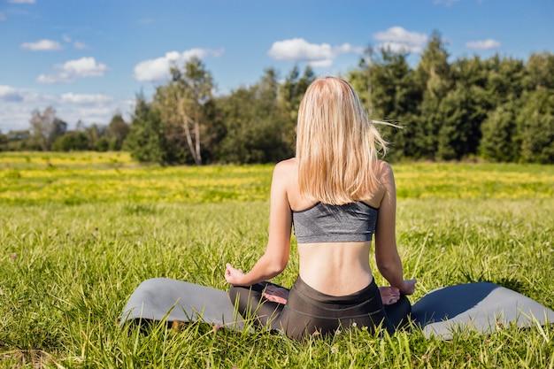 Jovem fêmea com braços abertos e longos cabelos loiros, sentado e relaxa em pose de ioga na natureza verde
