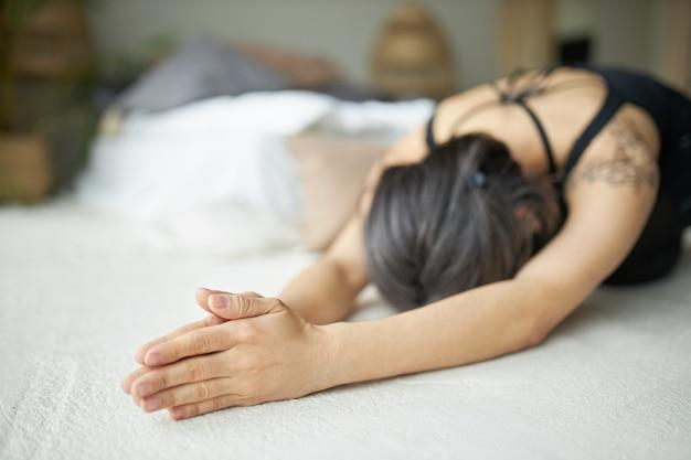 Jovem fêmea com cabelos grisalhos e tatuagem praticando ioga, alongando o corpo