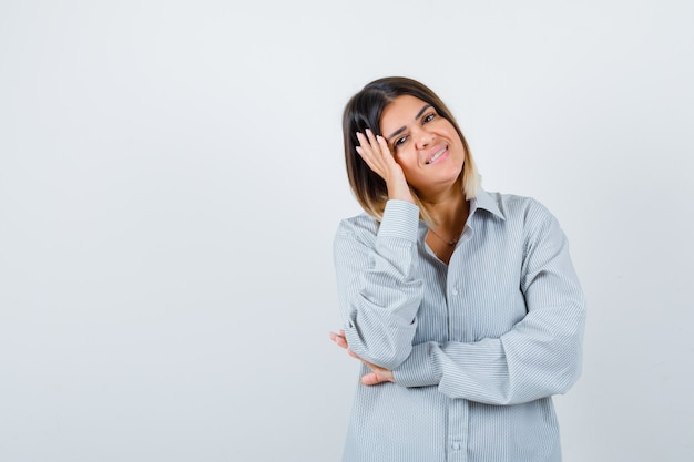 Jovem fêmea com camisa grande, descansando o rosto por lado e parecendo feliz, vista frontal.