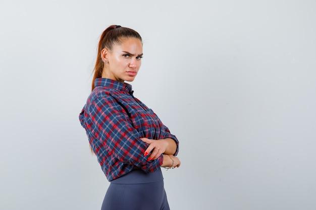 Jovem fêmea com camisa quadriculada, calça em pé com os braços cruzados e parecendo confiante, vista frontal.
