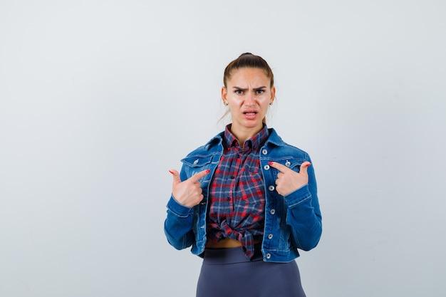 Jovem fêmea com camisa quadriculada, jaqueta, calças, apontando para si mesma e parecendo indefesa, vista frontal.
