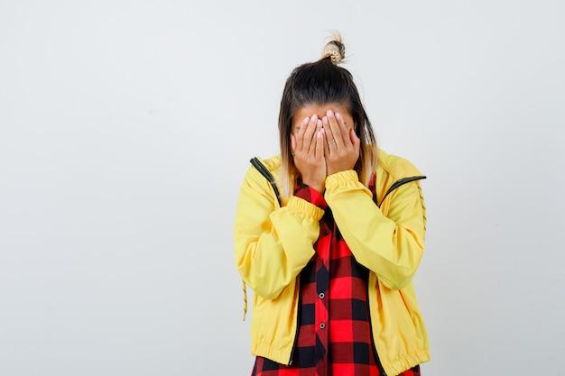 Jovem fêmea com camisa quadriculada, jaqueta cobrindo o rosto com as mãos e parecendo mal-humorada, vista frontal.