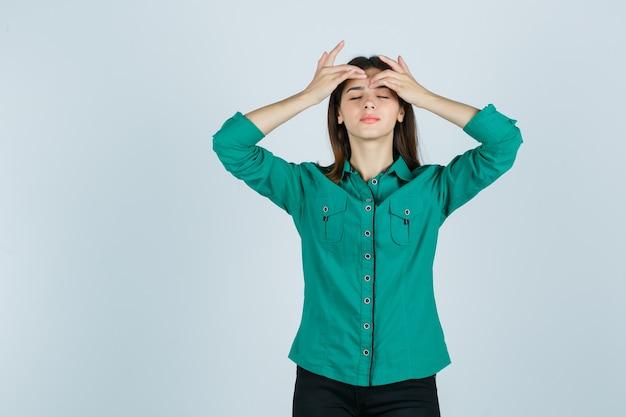 Jovem fêmea com camisa verde, apertando a espinha na testa e olhando relaxada, vista frontal.