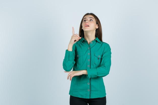 Jovem fêmea com camisa verde, apontando para cima e olhando maravilhada, vista frontal.
