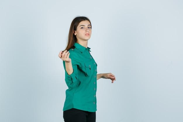 Jovem fêmea com camisa verde, fingindo segurar algo e olhando séria, vista frontal.
