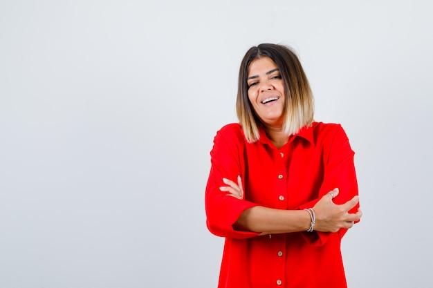 Jovem fêmea com camisa vermelha grande em pé com os braços cruzados e parecendo confiante, vista frontal.