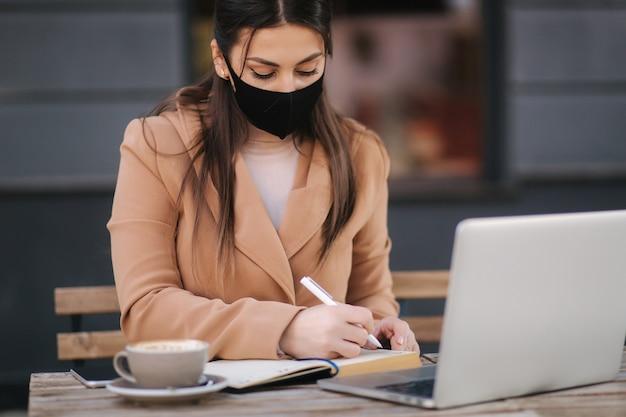 Jovem fêmea com máscara facial preta, sentada no terraço de uma cafeteria e escrevendo algo no caderno.