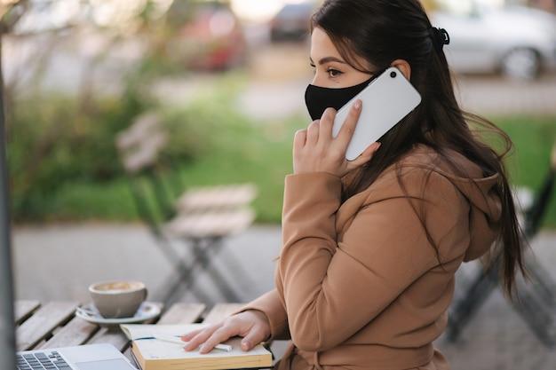Jovem fêmea com máscara facial preta sentada no terraço do café durante a quarentena. mulher fala ao telefone.