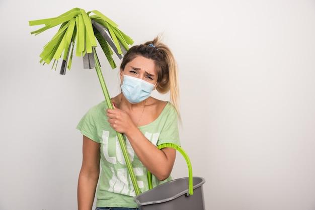 Jovem fêmea com máscara, segurando o esfregão na parede branca.
