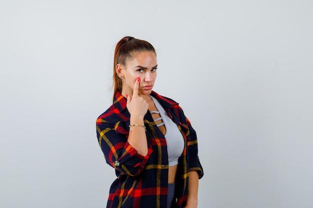 Jovem fêmea com o dedo na bochecha no top crop, camisa quadriculada, calças e bonita, vista frontal.