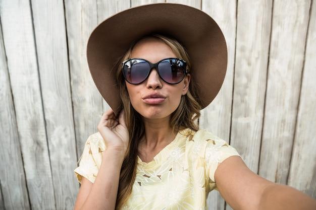 Jovem fêmea com óculos tomando selfie