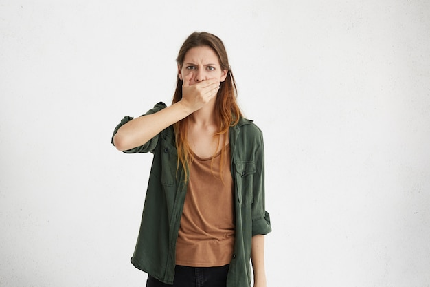 Jovem fêmea com olhos escuros e cabelo longo e reto, bocejando de tédio, segurando a mão na boca.