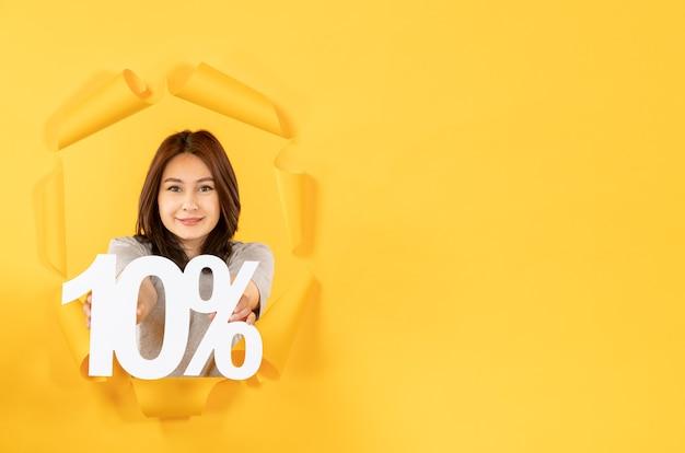 Jovem fêmea com placa de inscrição no fundo de papel amarelo rasgado, venda de dinheiro