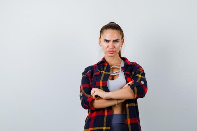 Jovem fêmea com top crop, camisa quadriculada, calça em pé com os braços cruzados e parecendo confiante, vista frontal.