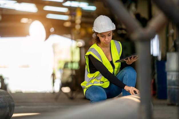 Jovem fêmea com uniforme de proteção, inspecionando a máquina industrial e tomando notas necessárias no tablet digital na fábrica.