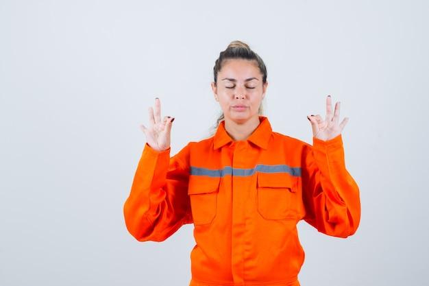Jovem fêmea com uniforme de trabalhador, meditando e olhando em silêncio, vista frontal.