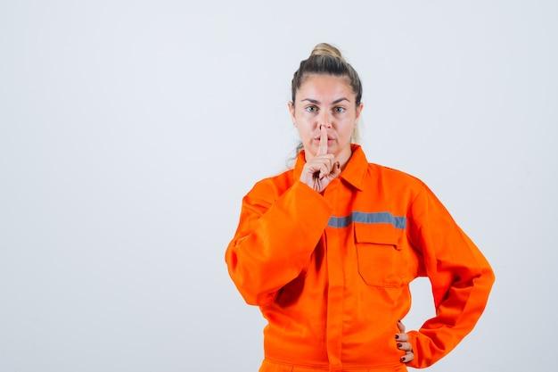Jovem fêmea com uniforme de trabalhador, mostrando gesto silencioso e parecendo exigente, vista frontal.