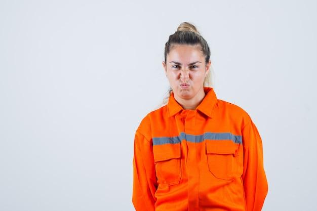 Jovem fêmea com uniforme de trabalhador olhando enquanto faz beicinho e olhando estranha, vista frontal.