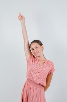 Jovem fêmea com vestido listrado, esticando o braço e olhando alegre, vista frontal.