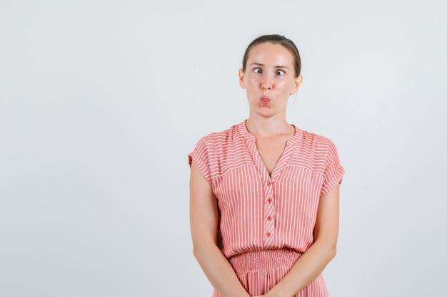 Jovem fêmea com vestido listrado, mostrando a língua e os olhos semicerrados e olhando engraçado, vista frontal.