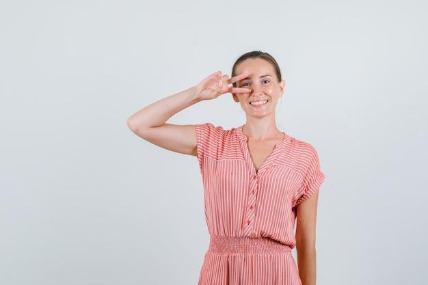 Jovem fêmea com vestido listrado, mostrando o sinal-v perto do olho e parecendo feliz, vista frontal.