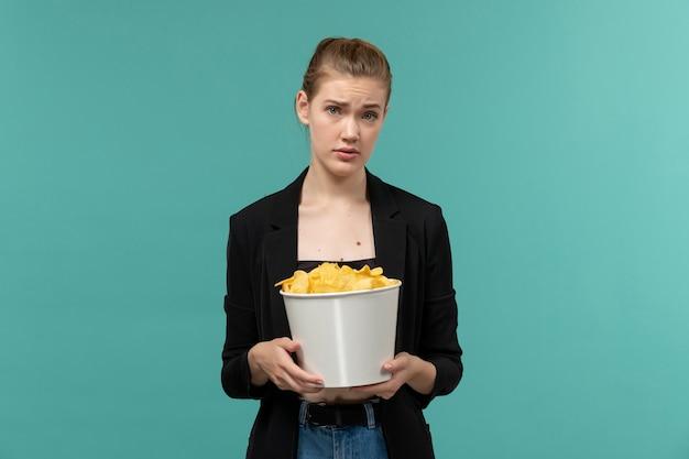 Jovem fêmea comendo batata frita assistindo filme na superfície azul