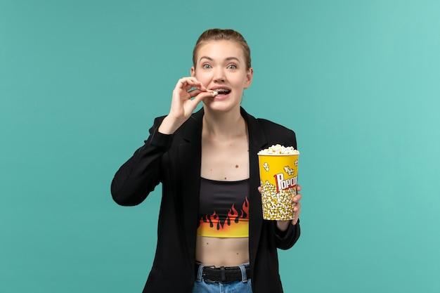 Jovem fêmea comendo pipoca e assistindo filme na superfície azul