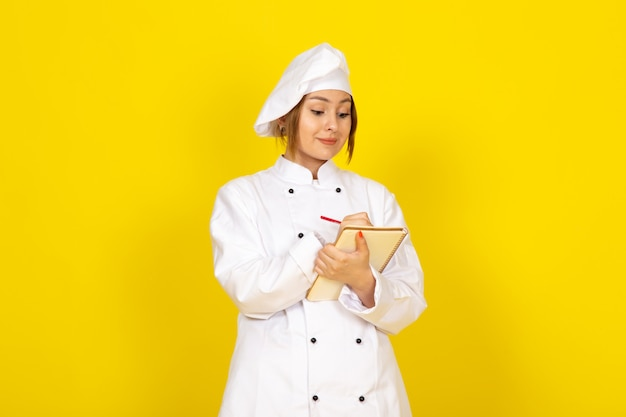 Jovem fêmea cozinhando em fato de cozinheiro branco e boné branco, anotando