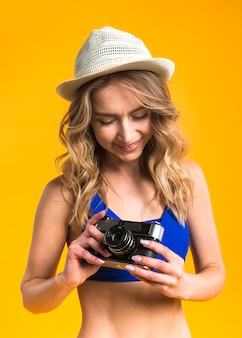 Jovem fêmea de biquíni está considerando a câmera