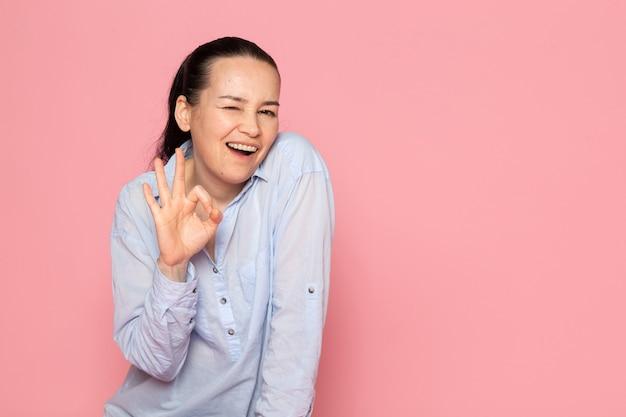 Jovem fêmea de camisa azul, posando na parede rosa