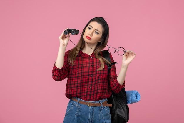Jovem fêmea de camisa vermelha com binóculos no modelo de foto de mulher de fundo rosa