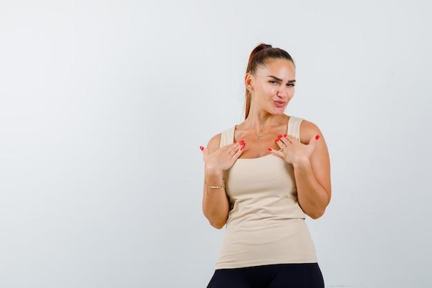 Jovem fêmea de mãos dadas no peito em um top bege e orgulhoso, vista frontal.