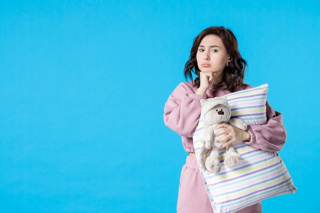 Jovem fêmea de pijama rosa com ursinho de brinquedo e travesseiro na noite azul de frente
