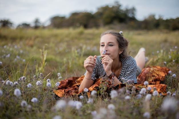 Jovem fêmea deitada em um campo de flores durante o dia