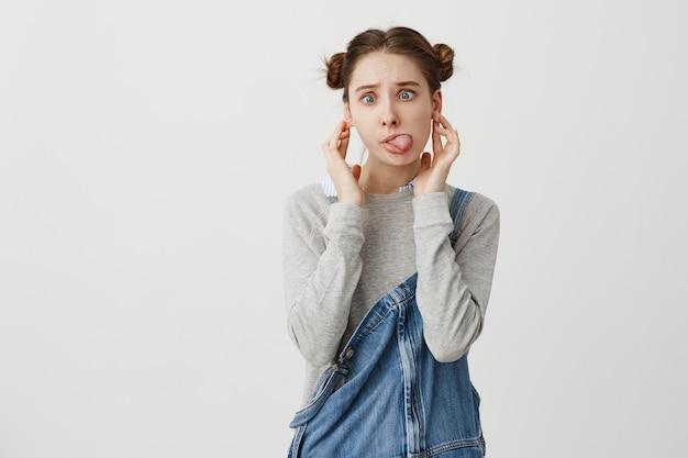 Jovem fêmea divertido expressar alegria e alegria com expressões faciais. jovem mulher com penteado odango, fazendo careta, colocando a língua para fora e se divertindo. emoções humanas positivas