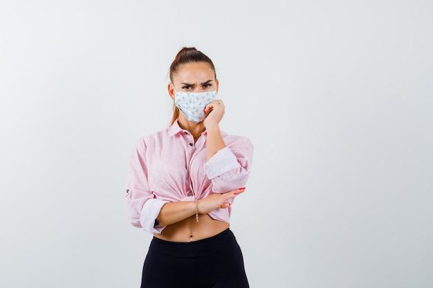 Jovem fêmea em camisa, calça, máscara médica, segurando a mão na bochecha e olhando pensativa, vista frontal.
